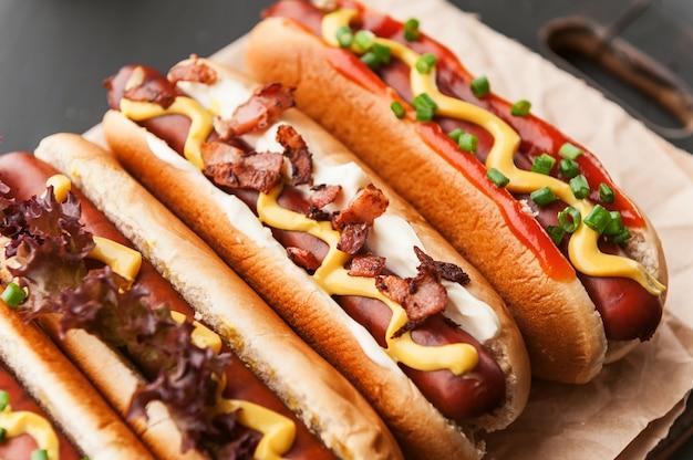 Barbacoa hot dogs a la parrilla con mostaza americana amarilla, sobre un fondo de madera oscura