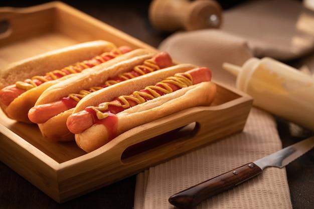 Barbacoa a la parrilla hot dog en madera, estilo oscuro.