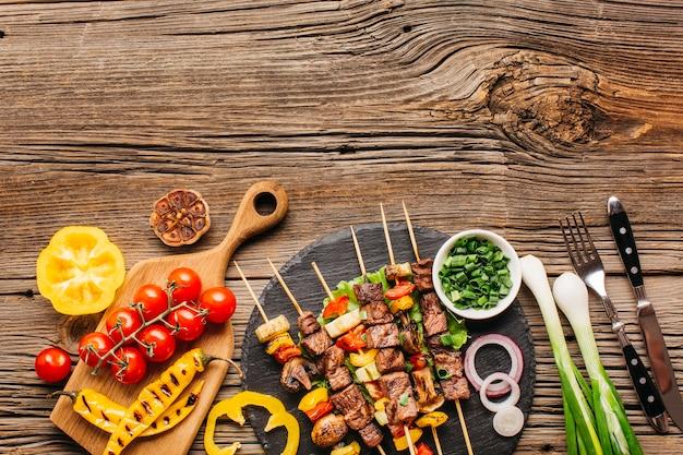 Barbacoa de pollo en brochetas con verduras sobre fondo de madera