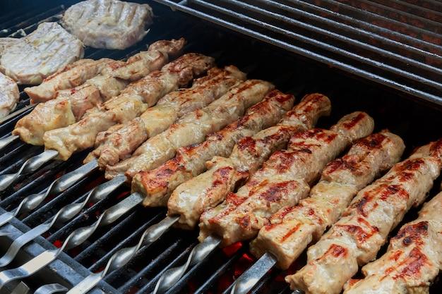 Barbacoa de shish kebab de pollo a la parrilla caliente fresca en rejilla sobre