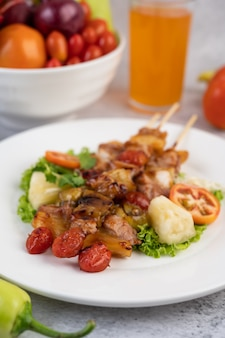 Barbacoa con una variedad de carnes, completa con tomates y pimientos en un plato blanco.
