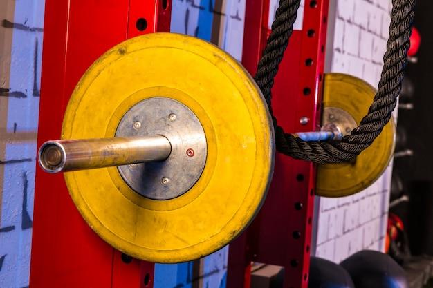 Barbells en un gimnasio, bar, campanas y cuerda.