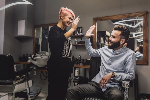 Barber y cliente dando alta cinco
