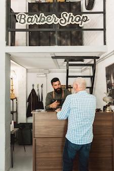 Barber hablando con el cliente en la recepción