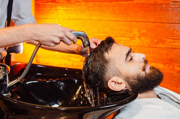 Barber lava la cabeza de un joven apuesto con barba y bigote en el fregadero
