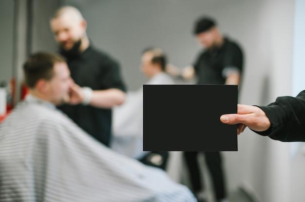 Barber tiene una tarjeta en blanco negra en la mano para copiar el espacio en el fondo de los clientes que recortan barberos. mano masculina que sostiene una tarjeta en blanco en el fondo de la barbería.