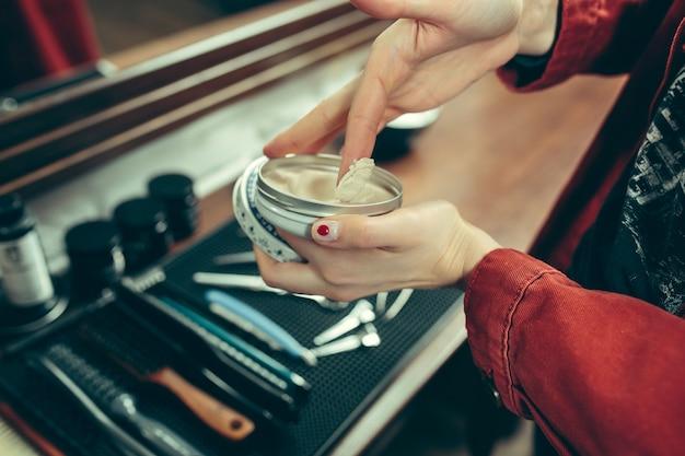 Barbería. peluquería femenina en el salón. igualdad de género. mujer en la profesión masculina. manos cerca