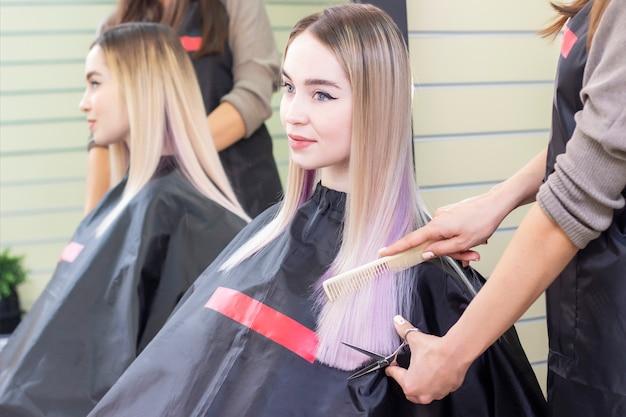 Barbería. el peluquero corta el cabello de una niña con unas tijeras. chica en un salón de belleza, cuidado del cabello