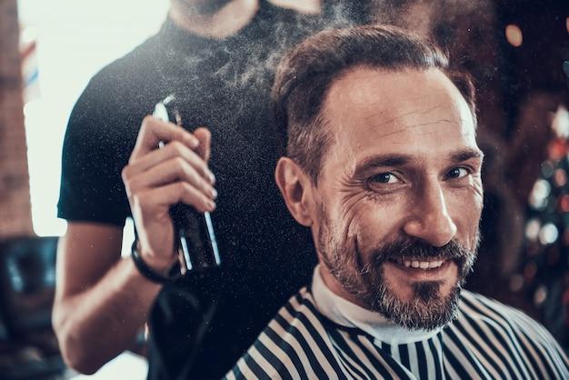 Barbero afeita guapo hombre sonriente con maquinilla de afeitar.