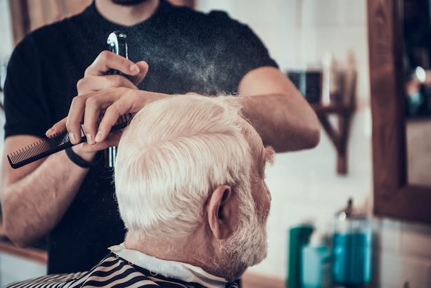El barbero afeita los lados adultos de cabello gris con maquinilla de afeitar
