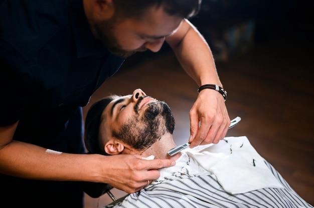 Barbero de alto ángulo afeitado barba del cliente