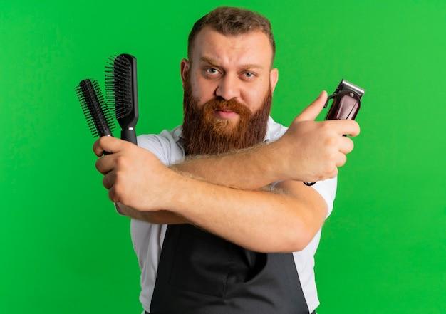 Barbero barbero profesional en delantal con máquina de afeitar y dos cepillos con expresión seria y segura de pie sobre la pared verde