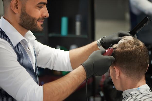 Barbero barbudo sonriendo y recortando el corte de pelo de su cliente masculino.