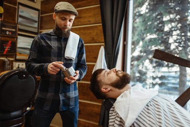 Barbero con cepillo y cliente barbudo, corte de barba. la peluquería profesional es una ocupación de moda