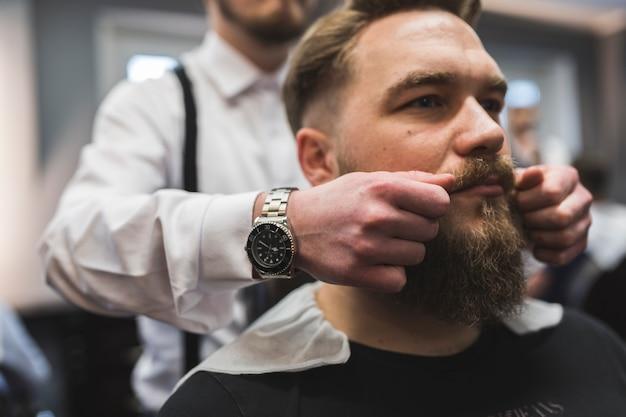 Barbero de la cosecha que tuerce el bigote del cliente