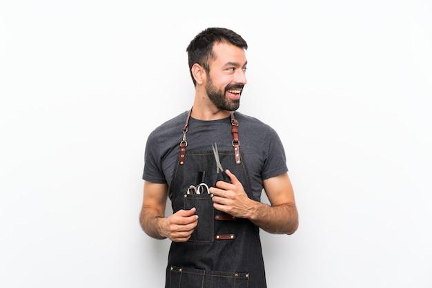Barbero en un delantal con los brazos cruzados y feliz
