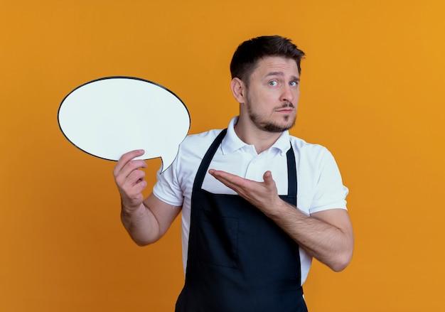 Barbero, hombre, en, delantal, tenencia, blanco, discurso, burbuja, señal, presentación, con, brazo, de, el suyo, mano, posición, encima, pared naranja