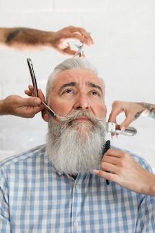 Barbero hombre envejecido visitando la peluquería