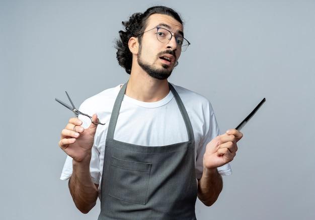 Barbero masculino caucásico joven impresionado con gafas y banda de pelo ondulado en uniforme sosteniendo tijeras y peine aislado sobre fondo blanco.