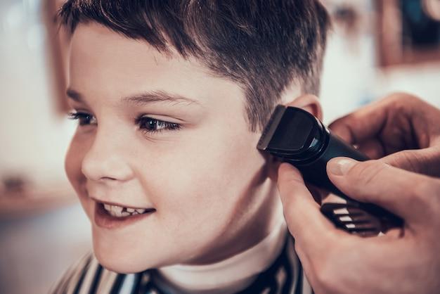 El barbero está recortando los lados del niño guapo con la maquinilla de afeitar