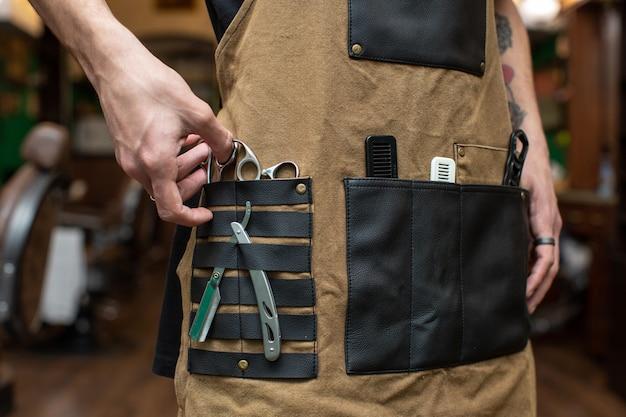 Barbero con varias herramientas en los bolsillos.