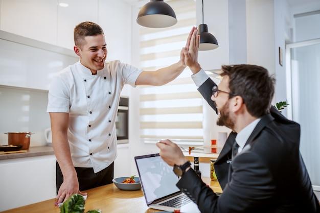 Barbudo hombre de negocios en traje sentado en la mesa del comedor, comiendo y dando cinco al chef para la comida perfecta. interior de la casa