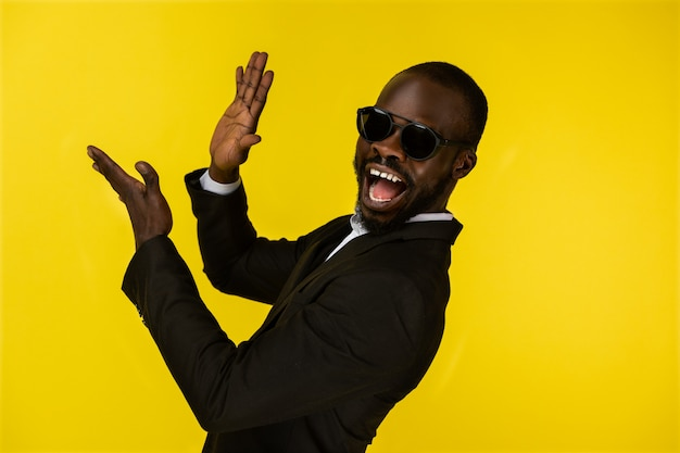 Barbudo joven afroamericano de lujo está aplaudiendo con gafas de sol y traje negro