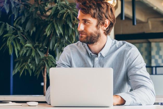 Barbudo joven empresario trabajando en la oficina moderna