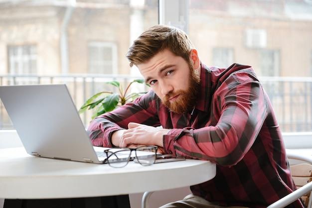 Barbudo joven sentado en la cafetería mientras usa la computadora portátil.
