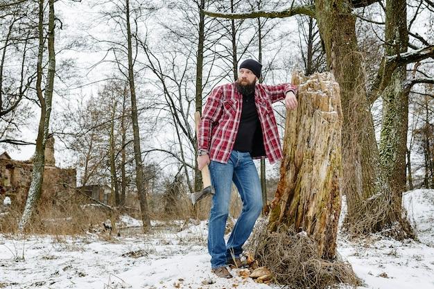 Barbudo loco con un hacha caminando por un camino nevado