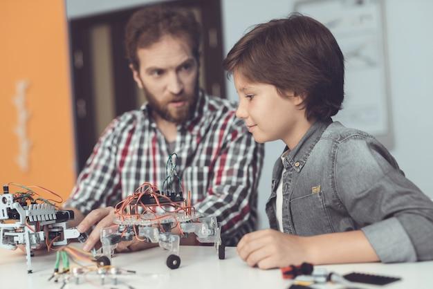 Barbudo padre e hijo construyendo robot en casa.
