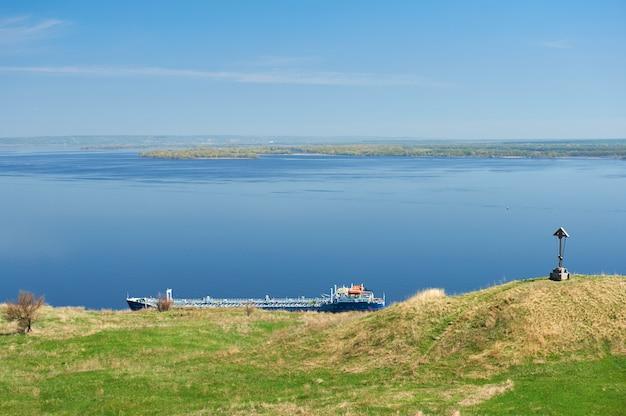 La barcaza vacía cerca de la orilla en el fondo del mar azul y el cielo.