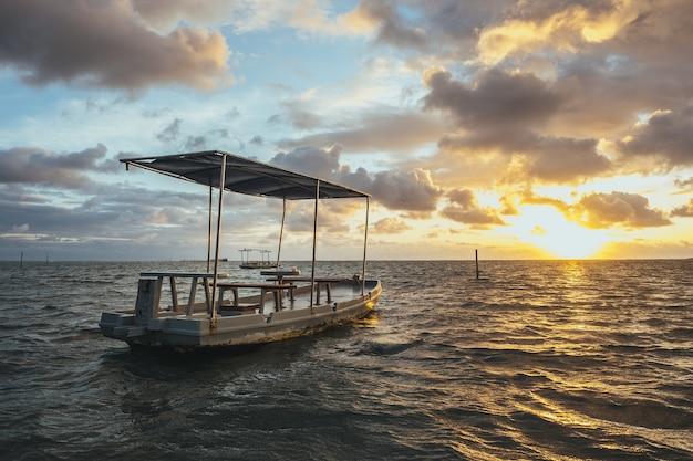 Barco artesanal de madera en el mar bajo un cielo nublado y la luz del sol durante la puesta de sol