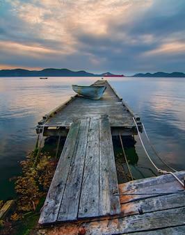 Barco azul en muelle de madera gris