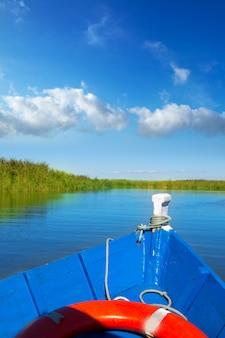 Barco azul navegando en albufera lago de valencia