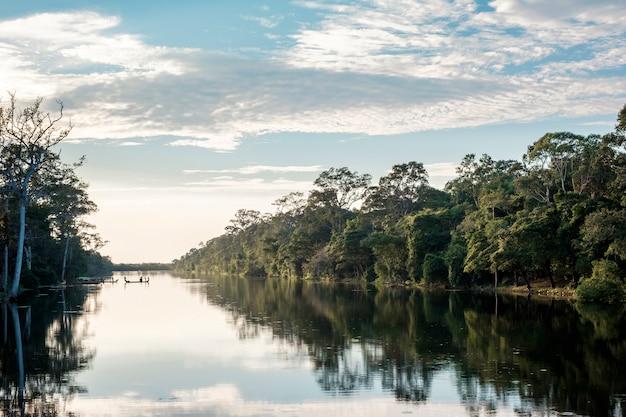 Barco, bosque, río y cielo azul en reflexión.