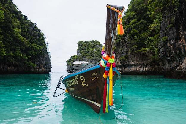 Barco de cola larga flotando en aguas transparentes de la isla phi-phi, la bahía maya, la isla paradisíaca en thailandia.
