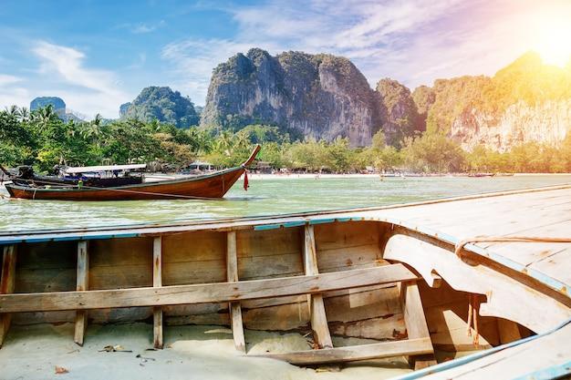 Barco de cola larga frente a la costa de una isla tropical con el telón de fondo de las montañas