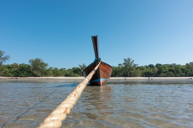 Barco de cola larga de madera tradicional tailandés y hermosa playa de arena.