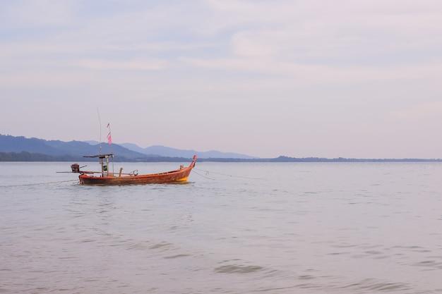 Barco de cola larga de pie cerca de la orilla al atardecer. hermosa puesta de sol del pueblo de pescadores en la bahía de phang nga con barco de pesca de madera de cola larga, tailandia. viaje por asia. paisaje con barco de pesca tradicional