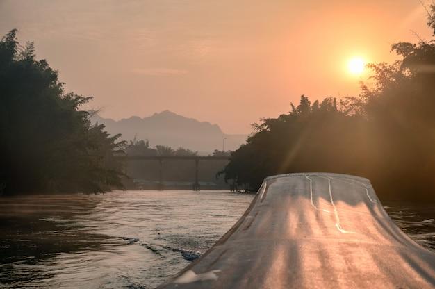 Barco de cola larga con salida del sol en el puente en el río kwai