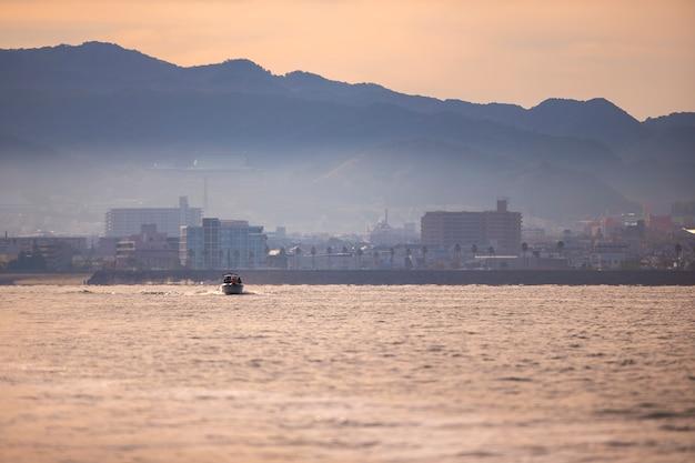 Barco corriendo hacia el mar en luz cálida en la bahía