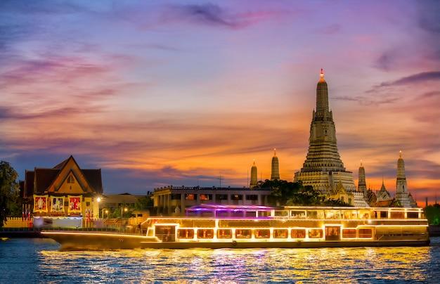 Barco de crucero por el río chao phraya con el templo del amanecer, wat arun, al atardecer en el fondo, horizontal