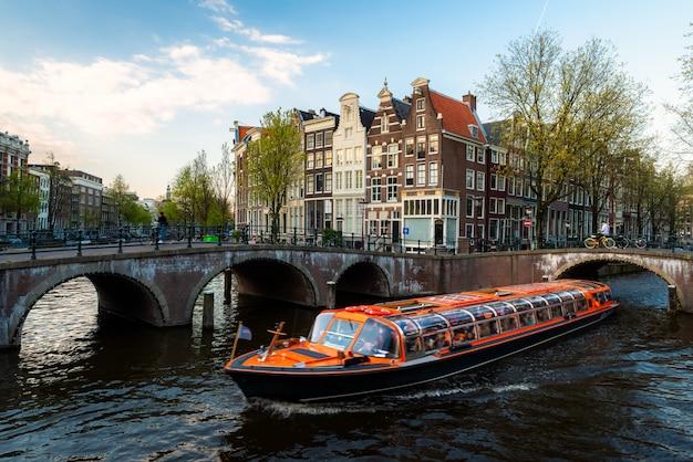 Barco de cruceros del canal de amsterdam con la casa tradicional holandesa en amsterdam, países bajos.