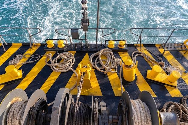 Barco de cubierta de ferry pintado de amarillo y negro junto con una gruesa cuerda de amarre