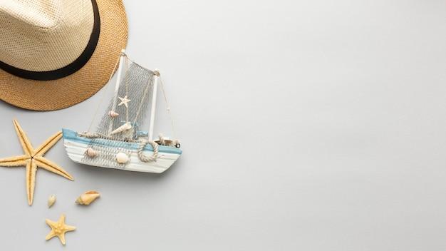 Barco, estrella de mar y sombrero de vista superior