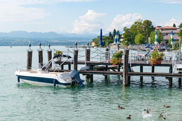 Barco flota en el agua en un muelle de madera en la costa de la ciudad turística