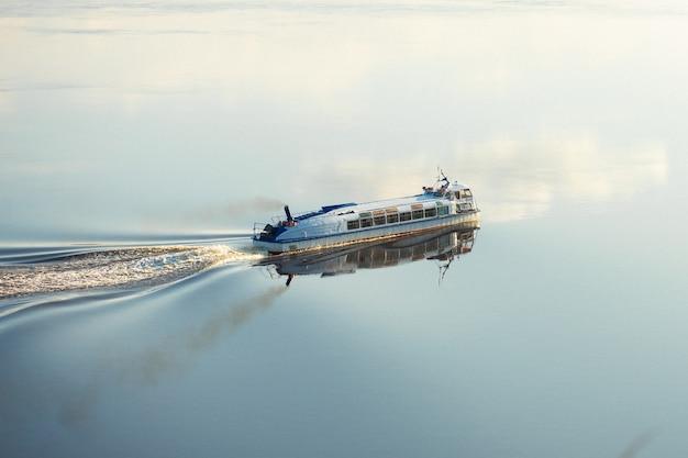 El barco fluvial de alta velocidad de pasajeros navega a lo largo del río hacia el atardecer.