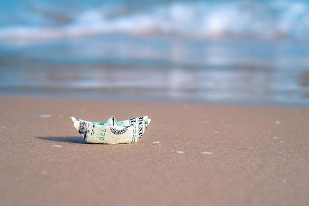 Un barco hecho de papel moneda en la arena del mar un barco fuera del dólar en el mar. arena de mar.