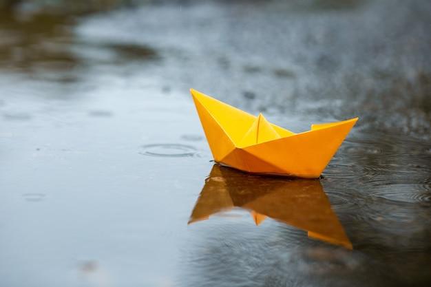 Barco de juguete amarillo hecho a mano de papel en un charco bajo la lluvia